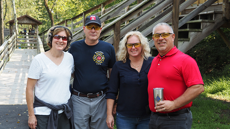 Group of participants smiling together after clay shooting